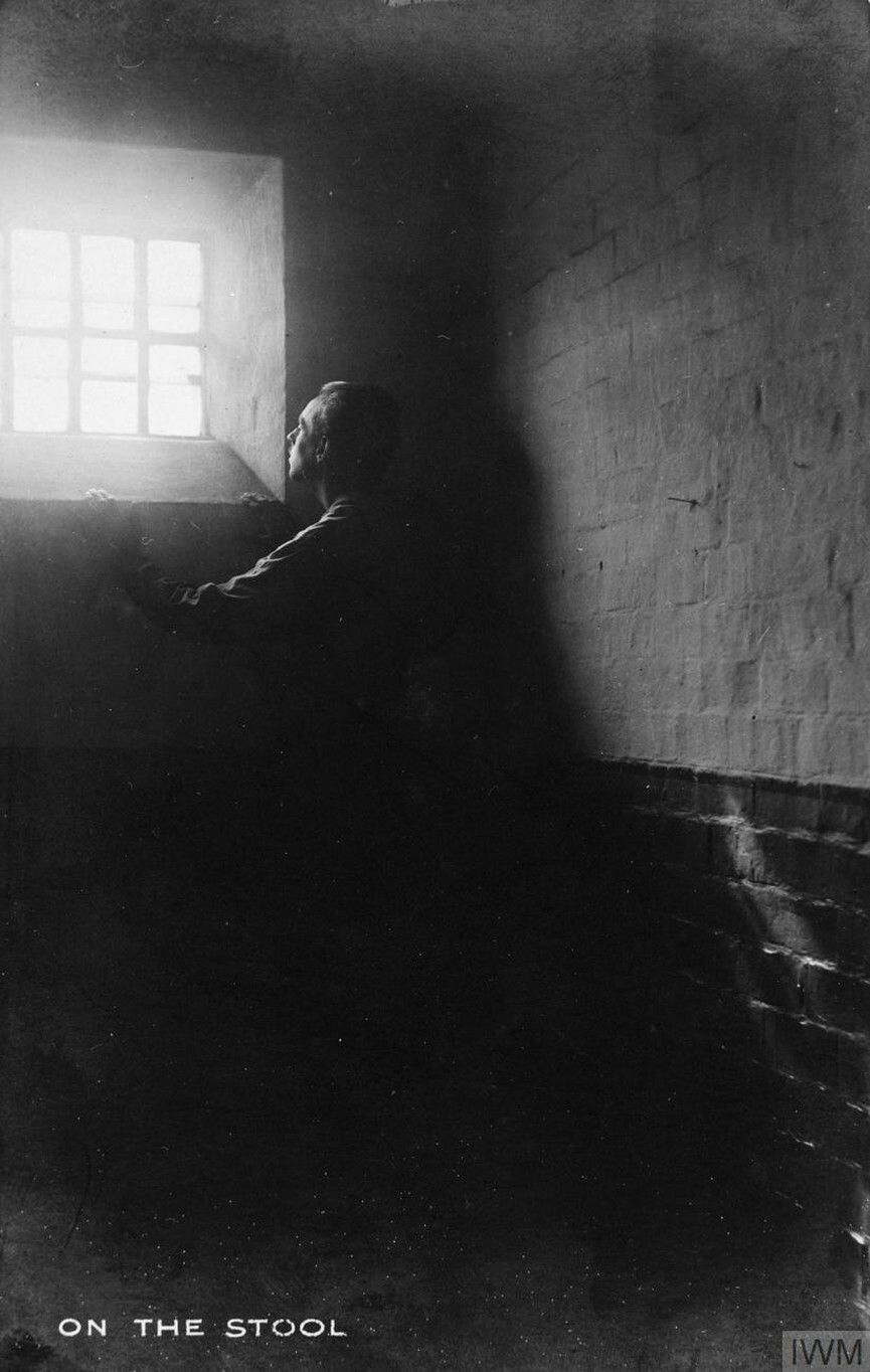 CO in Prison - Prisoner stands on a stool in a dark cell